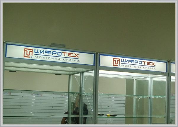 Оформление стеллажей в магазине цифровой техники рекламой